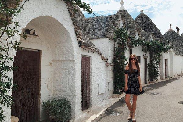 Victoria Lewis next to trulli huts in Alberobello.