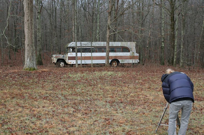 Mary shooting an old bus in the woods.