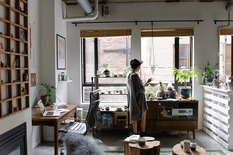 Girl in plant-filled room listening to music.