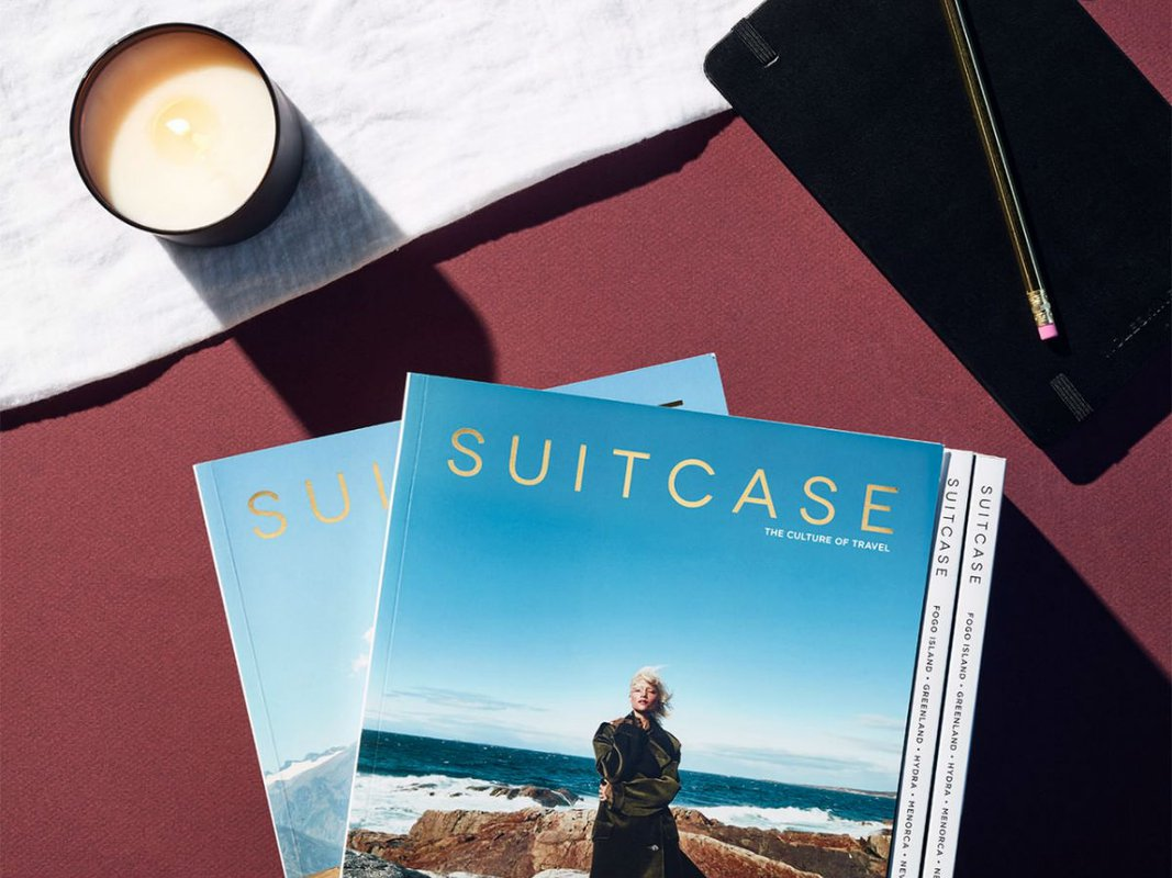 Suitcase magazine, notebook and candle