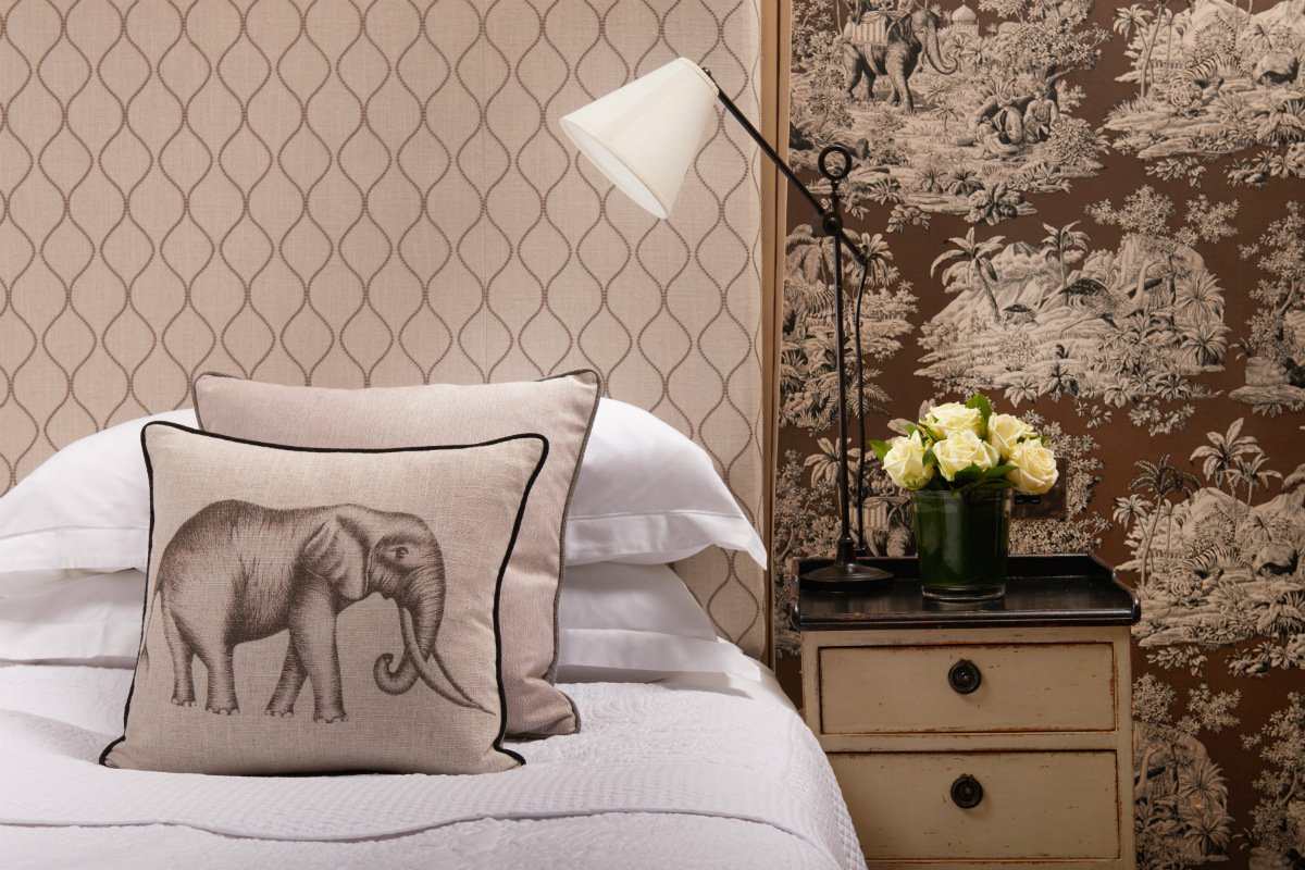 Patterned headboard, pillow, and wall laminate in a junior suite at at The Pelham London