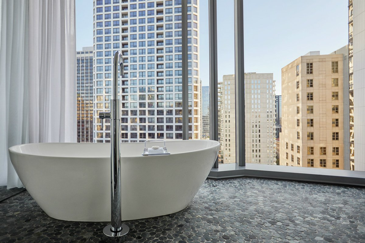 free standing bathtub with city skyline view at Viceroy Chicago