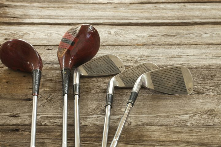 Antique Golf Clubs on Rough Wood Background
