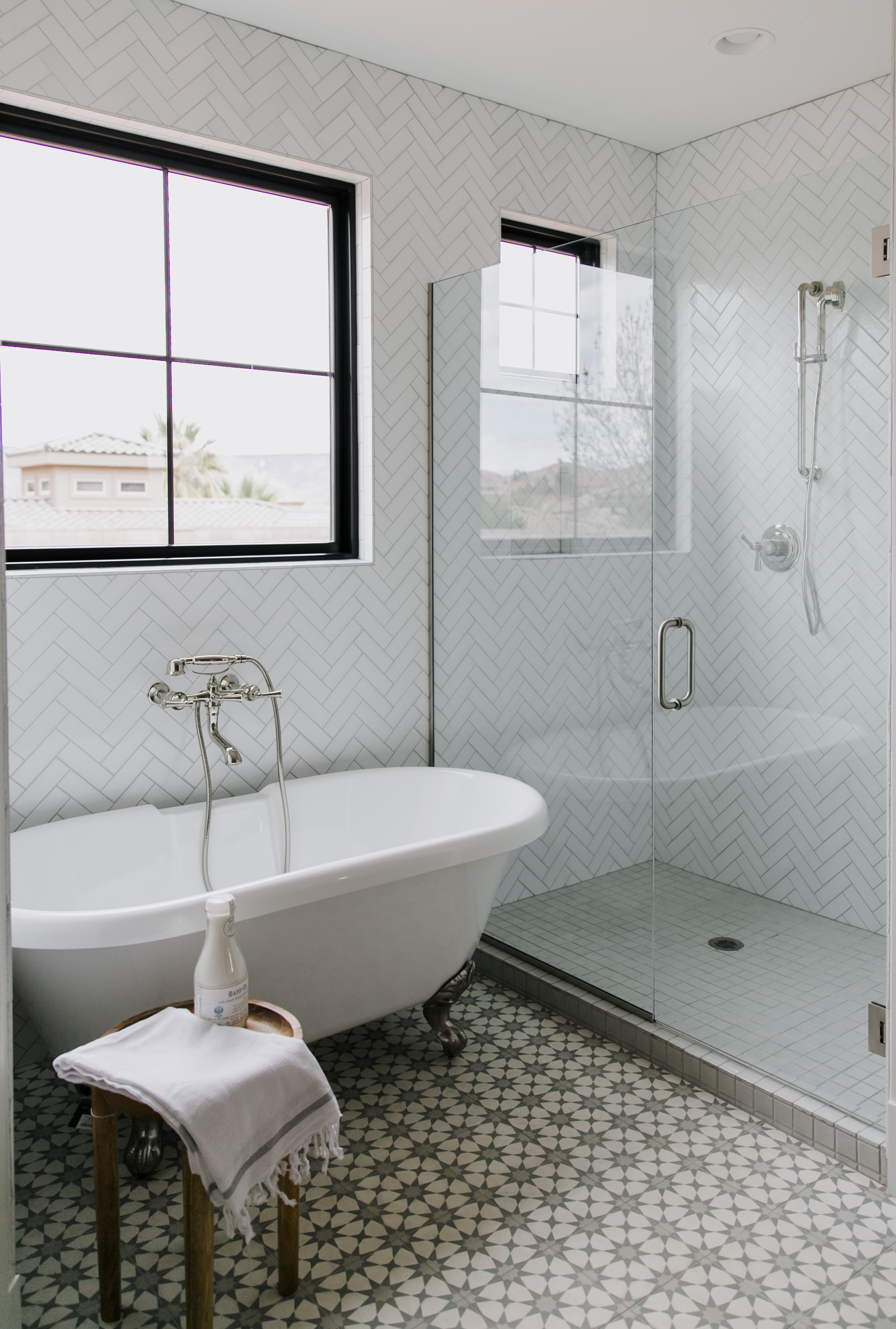 Ceramic and cement tiles in perfect harmony in this master bath that features our 2x6 tiles in White Wash in a herringbone pattern.