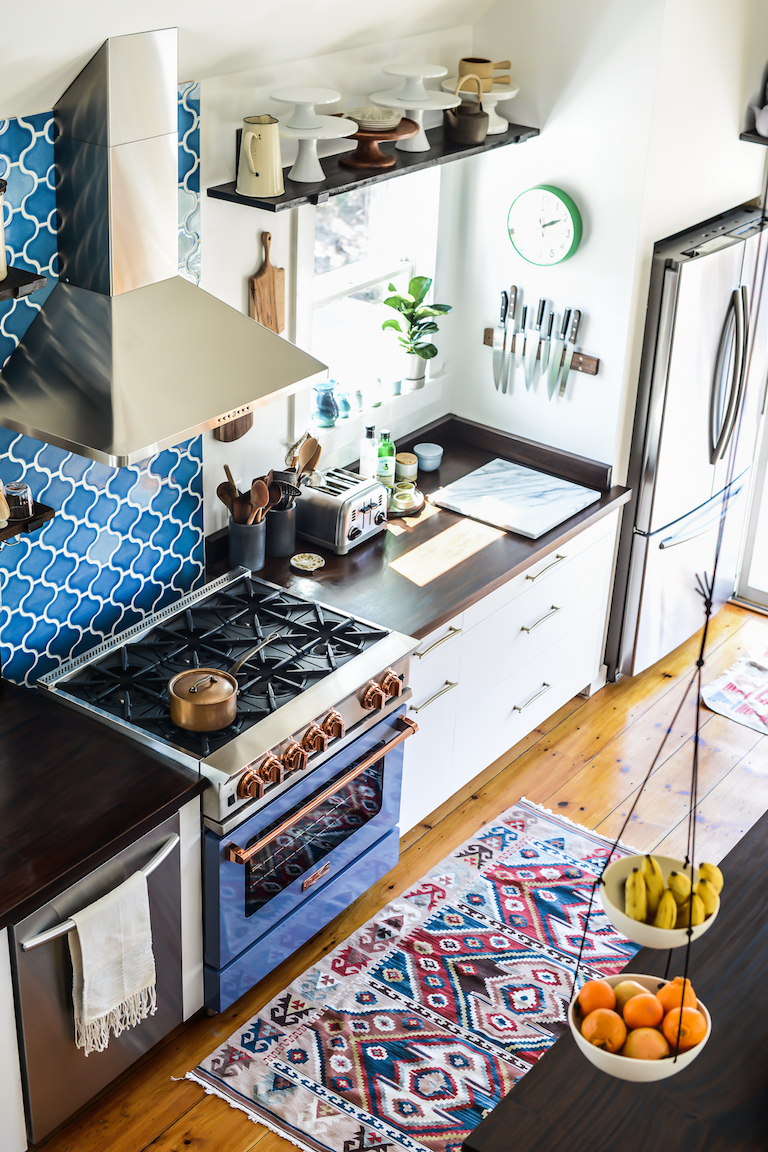 White and luxe wood finishes allow this bright blue backsplash tile to really pop.