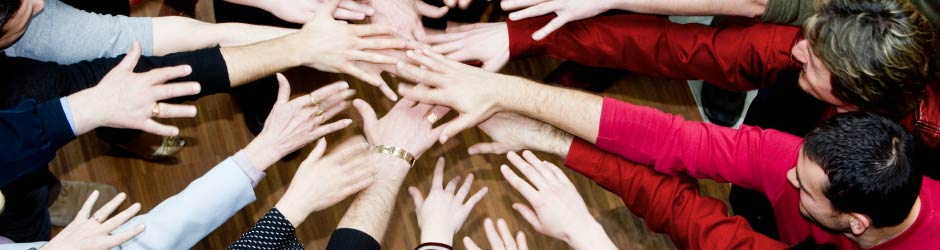 Hands reaching together in unity.