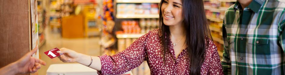 Una joven pagando con una tarjeta de First Federal
