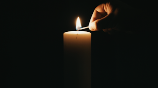 A hand is lighting a white candle in the dark thumbnail