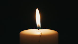 A white candle is flickering in the dark thumbnail