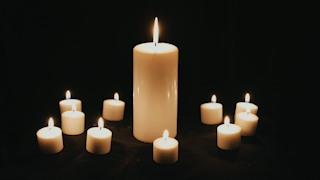 A group of white candles are burning in the dark thumbnail