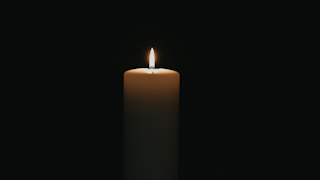 A white candle is burning in the dark thumbnail