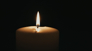 A large white candle is burning in the dark thumbnail