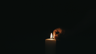 A match is lit and lights a white candle in the dark thumbnail