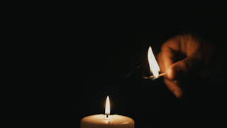 A match is lit and lights a large white candle in the dark thumbnail