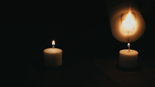A large candle is used to light two smaller candles in the dark thumbnail