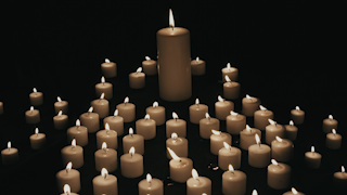 A large candle is surrounded by a group of smaller candles burning in the dark thumbnail