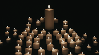 A large candle flickers and burns in the dark surrounded by smaller candles thumbnail