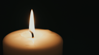 A large candle comes in and out of focus while burning in the dark thumbnail