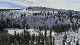 A snowy mountain rises above a frozen lake thumbnail