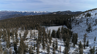 A small lake sits among snowy mountains and trees thumbnail