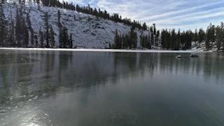 A frozen lake rests beneath a snowy mountain side thumbnail