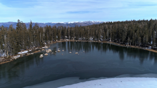 A lake sits among trees with snow and mountains thumbnail
