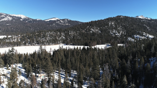 A snowy clearing surrounded by trees and mountains thumbnail