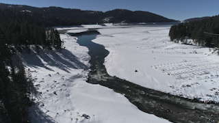 A river flowing into a lake surrounded by snow and trees thumbnail