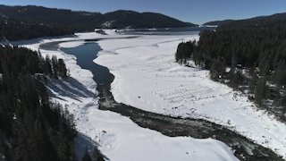 A river flows into a lake surrounded by trees and snow thumbnail