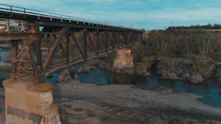 A train bridge runs across a small river gorge thumbnail