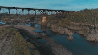 A train bridge runs across a river thumbnail