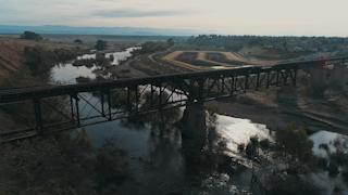 A train bridge runs across a river with mountains on the horizon thumbnail
