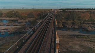 Train tracks run over a river gorge toward a green field thumbnail