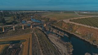 A train bridge runs across a river out in the countryside thumbnail