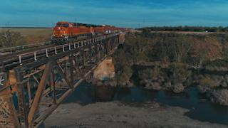 A train crosses a bridge over a river thumbnail