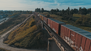 A train of red train cars journeys down railroad tracks thumbnail