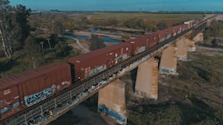 Red train cars travel down a train bridge thumbnail