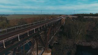 A metal train bridge crosses a river thumbnail