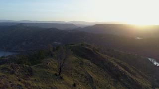 The sun rises over a mountainous terrain of green rolling hills thumbnail