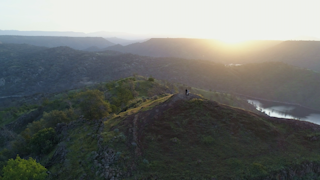 Two people stand on a mountain top at sunrise thumbnail