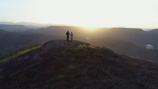 A man and woman watch the sunrise from on top of a green mountain thumbnail