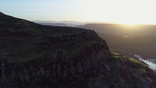 A rocky cliff edge is illuminated by the sunrise thumbnail