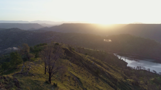 The sun rises over a mountainous terrain of green rolling hills surrounding a river thumbnail