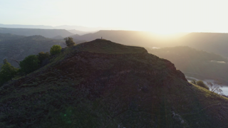 Two people stand on top of a green mountain top during the sunrise thumbnail