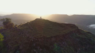 Two people stand on top of a mountain during a bright sunrise thumbnail