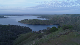 A lake sits among green hills and plains in the early morning thumbnail