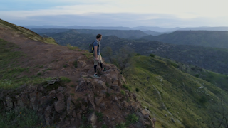 A man walks to the edge of a cliff with his phone during the early morning thumbnail