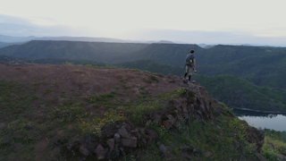 A man stands at the edge of a cliff overlooking a river at sunrise thumbnail