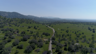 A road winds through a green countryside thumbnail