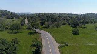 A road runs through a hilly green countryside thumbnail